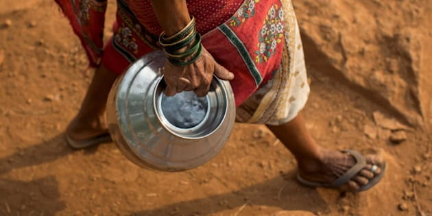 """Sakhri, second wife of Sakharam Bhagat, carries an empty metal pitcher as she walks to fetch water from a well outside her village in Denganmal, Maharashtra, India, April 20, 2015. In Denganmal, a village in Maharashtra state, some men take a second or third wife just to make sure their households have enough drinking water. Becoming what are known as """"water wives"""" allows the women, often widows or single mothers, to regain respect in conservative rural India by carrying water from the well quite some distance from the remote village. When the water wife, who does not usually share the marital bed, becomes too old to continue, the husband sometimes takes a third and younger spouse to fetch the water in metal pitchers or makeshift containers. REUTERS/Danish Siddiqui  PICTURE 12 OF 29 FOR WIDER IMAGE STORY """"WATER WIVES OF MAHARASHTRA""""??SEARCH """"WATER WIVES"""" FOR ALL IMAGES"""