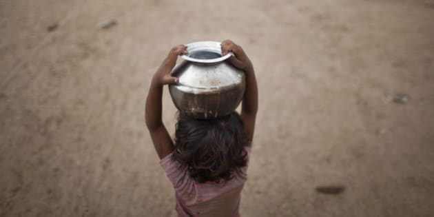Five-year-old Joshiya, carries a metal pitcher filled with water from a near-by well at Badarganj village in the western Indian state of Gujarat August 5, 2012. Armed with the latest monsoon rainfall data, weather experts finally conceded this month that India is facing a drought, confirming what millions of livestock farmers around the country had known for weeks. Picture taken August 5, 2012. To match feature INDIA-DROUGHT/ REUTERS/Ahmad Masood (INDIA - Tags: ENVIRONMENT SOCIETY AGRICULTURE BUSINESS)