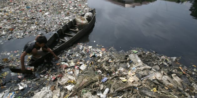 A boy collect plastics from a polluted river in Jakarta March 21, 2010. The Earth is literally covered in water, but more than a billion people lack access to clean water for drinking or sanitation as most water is salty or dirty. March 22 is World Water Day.   REUTERS/Supri  (INDONESIA - Tags: SOCIETY ENVIRONMENT)