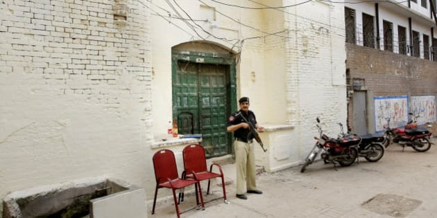 In this Monday, April 25, 2016 photo, a Pakistani policeman stands guard outside the 300-year-old gurdwara or place of worship for Pakistan's Sikh minority, in Peshawar. While Sikhs celebrated the opening of their gurdwara, its neighbors all of whom are Muslim told The Associated Press that they either didn't want them there or were worried that an attack by militants was certain to happen. (AP Photo/Mohammad Sajjad)