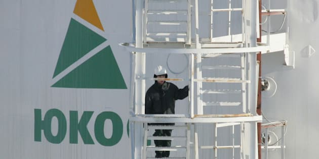 A worker climbs up the stairs of an oil container at the pumping station near the Priobskoye oil field, some 150 km from the Siberian town of Khanty-Mansiysk, March 22, 2005. Priobskoye was a jewel field in the crown of oil firm Yugansk, formerly a key oil producing unit of oil major YUKOS. Yugansk was re-nationalised last December to recover YUKOS's back taxes and is now controlled by state oil firm Rosneft. Picture taken March 22, 2005. REUTERS/Sergei Karpukhin  CVI/SM
