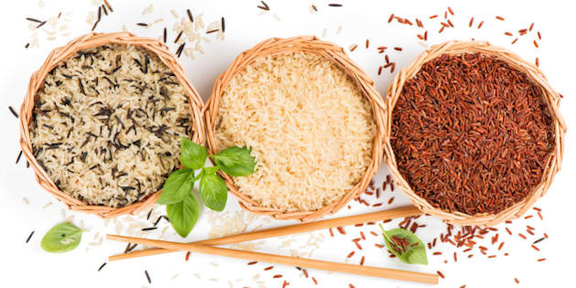 Top view of different rice types in a baskets decorated with basil  and chopsticks isolated on white background