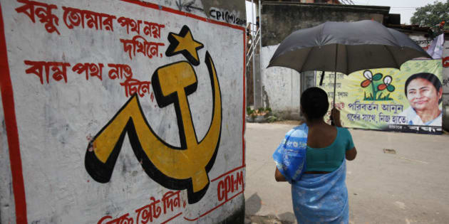 A woman carrying an umbrella walks past political murals and posters in Kalighat district, the neighbourhood where Trinamool Congress leader Mamata Banerjee lives, in Kolkata May 12, 2011. The murals feature slogans in support of the the Marxist Left Front (L) and Trinamool Congress with a portrait of Banerjee (R). Exit polls show the 56-year-old Banerjee will win a landslide vote when ballots are counted on Friday to become the next leader of this state of 90 million, a population equivalent to Germany.  REUTERS/Danish Siddiqui (INDIA - Tags: POLITICS ELECTIONS)