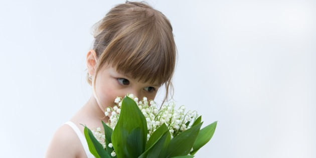 little girl holding bunch of lilies of the valley