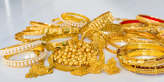 Gold jewellery or jewelry including pure gold bangles and gold with pearl bangles, rings, ear rings, lockets, etc on white marble floor.