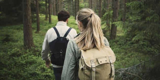 Rear view of wonderlust couple walking through forest