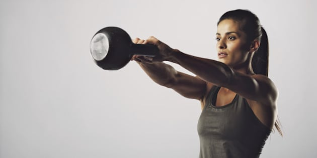Young fitness female exercise with kettle bell. Mixed race woman doing gym workout on grey background