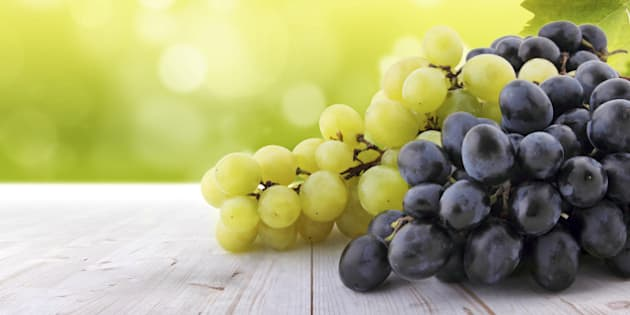 Wine collection: White and red grapes on table in vineyard. Blurred lights in background.