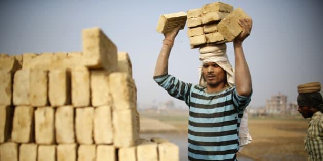 An Indian migrant worker stack bricks on his head at a brick factory in Lalitpur, Nepal January 11, 2016. REUTERS/Navesh Chitrakar