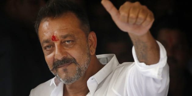 Bollywood actor Sanjay Dutt shows a thumbs up sign after arriving at his residence in Mumbai, India, Thursday, Feb. 25, 2016. Actor Dutt walked free Thursday after completing his five-year prison sentence for illegal weapons possession in a case linked to the 1993 terror attack in India's financial capital Mumbai. (AP Photo/Rajanish Kakade)