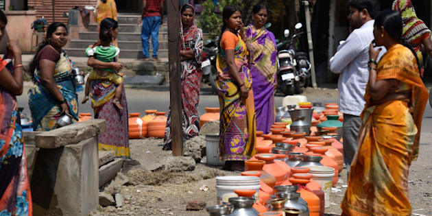 LATUR, INDIA - MARCH 23: People lined up with their pots to collect drinking water from government boring on March 23, 2016 in Latur, India. Of the total 1,133 farmers committed suicide in the region due to causes ranging from crop failure from lack of water to inability to meet loan payments, reported across the eight districts of Marathwada last year, 301were from Beed district. Summer's just beginning but temperatures are already crossing 40 degrees Celsius in Beed, Latur and Osmanabad, the three districts worst-hit by the drought that is ravaging Marathwada. For the 65 lakh people who live there, it's a struggle to get even their daily ration of 20 litres of water, hardly a bucketful. According to officials, of the 75 medium dams in Marathwada, 54 have completely dried up. The state had also declared drought in a few thousand villages in Vidarbha. The Maharashtra Govt's Jalyukt Shivar scheme, which plans to make the state drought free by 2019 by widening streams and dam construction, may be underway but with barely 2 per cent water remaining in dams across Beed district, the scheme may find it difficult to prove its impact. (Photo by Arijit Sen/Hindustan Times via Getty Images)