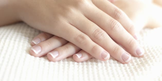 Woman folds her well manicured hands as she lays downs and enjoys a spa treatment