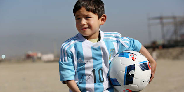 Murtaza Ahmadi, a five-year-old Afghan Lionel Messi fan poses for photograph, as he wears a donated shirt signed by Messi, in Kabul, Afghanistan, Friday, Feb. 26, 2016.  (AP Photo/Rahmat Gul)