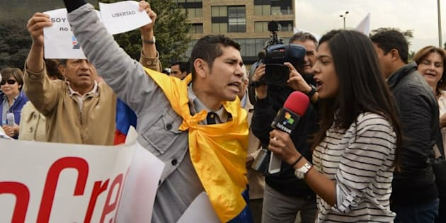A supportern (L) of former presidential candidate Oscar Ivan Zuluaga insults Telesur journalist Natalia Margarita (R) during a rally to show him their encouragement as he arrives to questioned at the prosecutor's office  in Bogota, Colombia, on January 30, 2015. Zuluaga will be questioned about hacker Andres Sepulveda, who worked for him during his presidential campaign and is currently pointed as having leaked sensitive army information with the intent of sabotaging the peace process with the FARC. The placard reads 'The Prosecutor is a Friend to the FARC'.   AFP PHOTO/Luis Acosta        (Photo credit should read LUIS ACOSTA/AFP/Getty Images)
