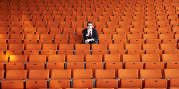 A curious man sitting in an empty auditorium