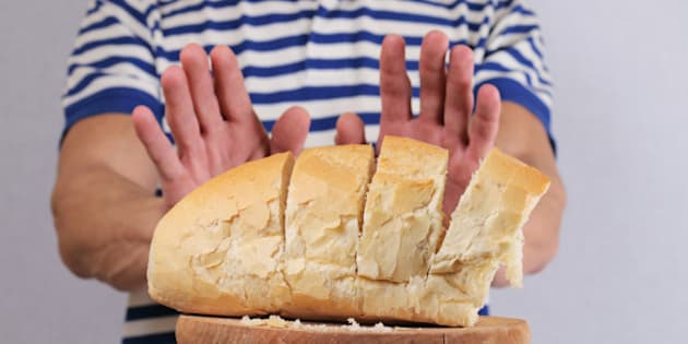 Gluten intolerance and diet concept. Man refuses to eat white bread. Selective focus on bread