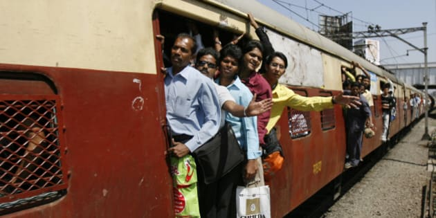 Commuters hang out of the crowded compartments of a local train while travelling in Mumbai February 26, 2007. India on Monday cut some 2007/08 freight rates to combat inflation and encourage rail use and trimmed passenger fares for its rail network, one of the world's largest, to provide cheaper transport for the poor.   REUTERS/Punit Paranjpe  (INDIA)