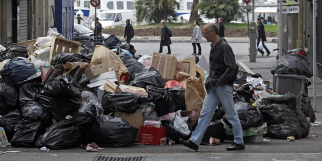 A man walks past piled up garbage at the Old Port of Marseille October 24, 2010 on the 13th day of a strike by rubbish collectors.  REUTERS/Jean-Paul Pelissier (FRANCE - Tags: EMPLOYMENT BUSINESS POLITICS CIVIL UNREST)