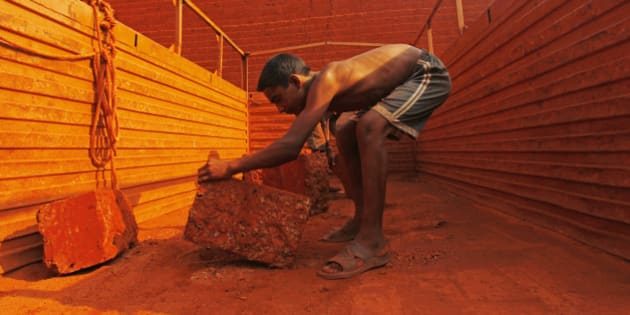 Sunil, 14, loads a brick onto the back of a truck at a laterite brick mine in Ratnagiri district, about 360km (224 miles) south of Mumbai, April 14, 2011. Sunil is paid two Indian rupees ($0.04) per brick and carries an average of 100 bricks out of the mine per day. Each brick costs between 10-14 rupees ($0.22-$0.31), and weighs around 40 kg. REUTERS/Danish Siddiqui (INDIA - Tags: SOCIETY EMPLOYMENT BUSINESS)