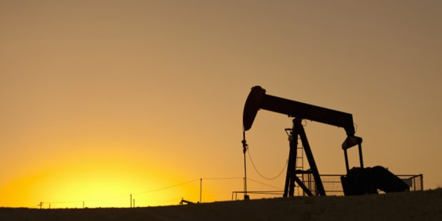 Oil pump working in an extensive oil field at sunset.