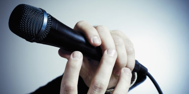 Close-up of a person's hand holding a microphone