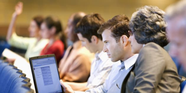 Business people sitting in lecture hall with laptop
