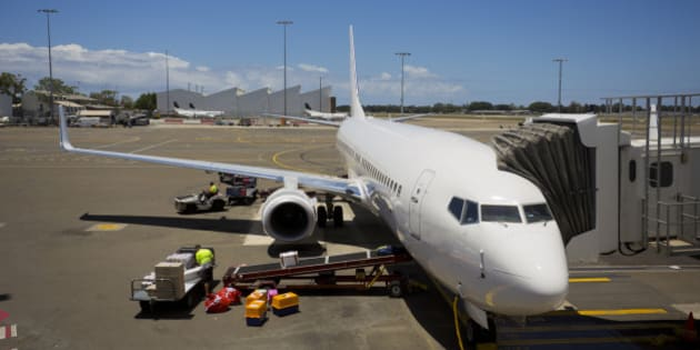 Jet aeroplane being loaded while waiting for boarding passengers at a terminal gate aerobridge