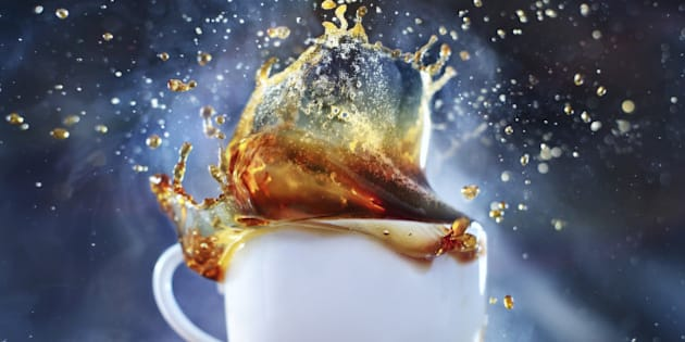 Great splash in the cup of coffee on a blue background.