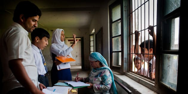 SRINAGAR, KASHMIR, INDIA - SEPTEMBER 01: Arshida Siddiqui, a senior teacher without a disability, teaches deaf and mute students using sign language at Abhedananda Home, a school for deaf, mute and blind students on September 1, 2015 in Srinagar, the summer capital of Indian administered controlled Kashmir State, India. The school is having difficulty owing to a lack of funds after the government stopped grants to it. The school was established  in 1941 and presently teaches 100 special needs children. It was severely damaged in last years September floods, which killed over 200 and damaged property costing billions of dollars. The government declined any help to restore the infrastructure at this school, school authorities said.  Disability is an important public health problem, especially in developing countries like India where a majority of the disabled live where accessibility, availability, and utilization of rehabilitation services and its cost-effectiveness are major issues. (Photo by Yawar Nazir/Getty Images)