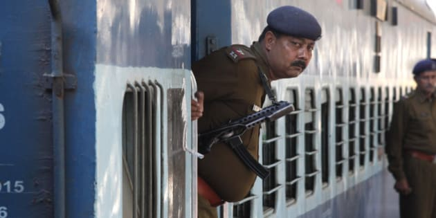 A Railway Police personnel peeps out from the door of a special passenger train at a railway station in Chandigarh, India, February 22, 2016. REUTERS/Ajay Verma