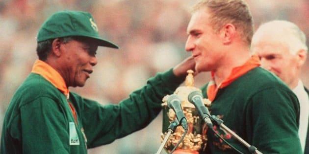le capitaine de l'équipe de rugby d'Afrique du Sud, François Pienaar (D) est félicité par le Président de la République Sud-africaine, Nelson Mandela (G), après la victoire de son équipe en finale de la Coupe du Monde de Rugby face à la Nouvelle-Zélande le 24 juin 1995 à Johannesburg.South African rugby team captain, Francois Pienaar (R), is congratulated by South African President Nelson Mandela (L) after South Africa won the Rugby World Cup final against New Zealand 24 June 1995 in Johannesburg.        (Photo credit should read JEAN-PIERRE MULLER/AFP/Getty Images)