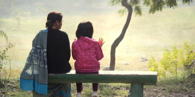 A child sitting with her grandmother on a bench in the park.