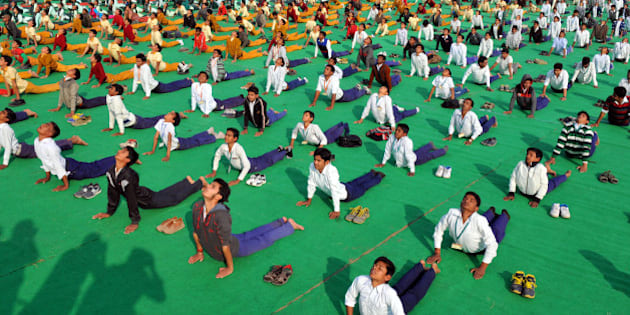 INDORE, INDIA - JANUARY 12: School students participate in Surya Namaskar function organized at Chiman Bagh Ground on the occasion of Swami Vivekanand Jayanti on January 12, 2016 in Indore, India. Surya Namaskar along with Pranayam will be held in all schools, colleges, panchayats and ashram shalas across the state. (Photo by Shankar Mourya/Hindustan Times via Getty Images)