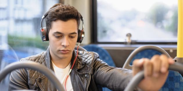 Mixed race man listening to headphones on bus