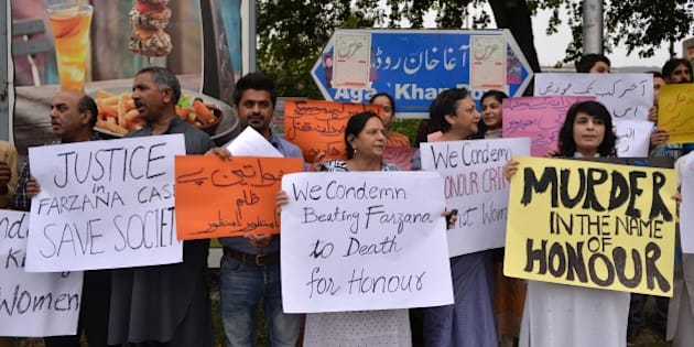 Pakistani human rights activists hold placards as they chant slogans during a protest in Islamabad on May 29, 2014 against the killing of pregnant woman Farzana Parveen was beaten to death with bricks by members of her own family for marrying a man of her own choice in Lahore. Pakistan's prime minister demanded 'immediate action' over the brutal murder of a pregnant woman who was bludgeoned to death with bricks outside a courthouse while police stood by. Farzana Parveen was attacked on May 27 outside the High Court building in the eastern city of Lahore by more than two dozen brick-wielding attackers, including her brother and father, for marrying against the wishes of her family. AFP PHOTO/Aamir QURESHI        (Photo credit should read AAMIR QURESHI/AFP/Getty Images)