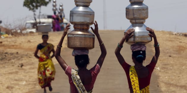 Indian women walk home after collecting drinking water from a well at Mengal Pada  in Thane district in Maharashtra state, India, Wednesday, May 4, 2016. Much of India is reeling under a weekslong heat wave and severe drought conditions that have decimated crops, killed livestock and left at least 330 million Indians without enough water for their daily needs. (AP Photo/ Rajanish Kakade )
