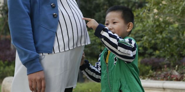 HANGZHOU, CHINA - OCTOBER 13:  (CHINA OUT) A boy touches his pregnant mother's belly on October 13, 2014 in Hangzhou, China.  (Photo by VCG/VCG via Getty Images)