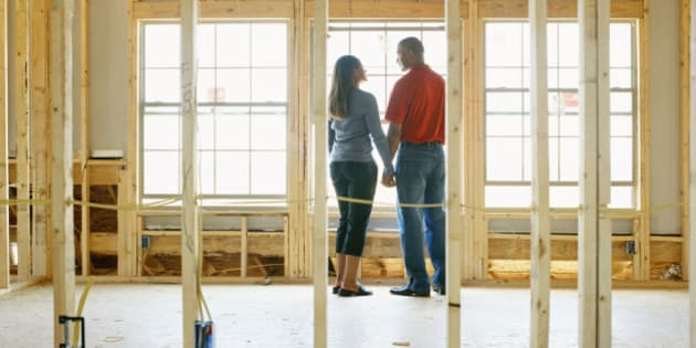 Couple holding hands in home under construction, rear view