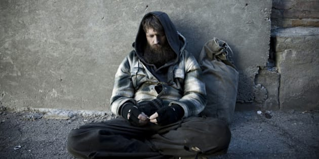 USA, Utah, Salt Lake City, Homeless man with sack sitting on sidewalk