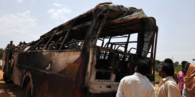 Villagers inspect a burnt-out passenger bus of the Karnataka State Road Transport Corporation (KSRTC) in Challakere village, Chitradurga district around 220 kms north of Bangalore on May 30, 2010. At least 30 people, including 10 children, were burnt alive when a bus bound for the southern Indian city of Bangalore ploughed into a roadblock and caught fire, police said. AFP PHOTO/Dibyangshu Sarkar (Photo credit should read DIBYANGSHU SARKAR/AFP/Getty Images)