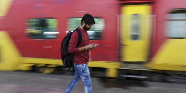 A passenger walks past a train while using a smartphone at Mumbai Central railway station in Mumbai, India, on Friday, Jan. 22, 2016. Google Inc. in partnership with RailTel Corp. and Indian Railways today launched high speed WiFi at the station. They plan to roll out the service to more than 400 railway stations, covering 10 million passengers each day, according to chief executive officer Sundar Pichai. Photographer: Dhiraj Singh/Bloomberg via Getty Images