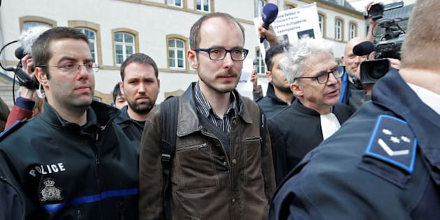 Former PricewaterhouseCoopers employee Antoine Deltour (C) and his lawyer William Bourdon (R) are escorted by police as they leave the court after the first day of the LuxLeaks trial in Luxembourg, April 26, 2016. REUTERS/Vincent Kessler