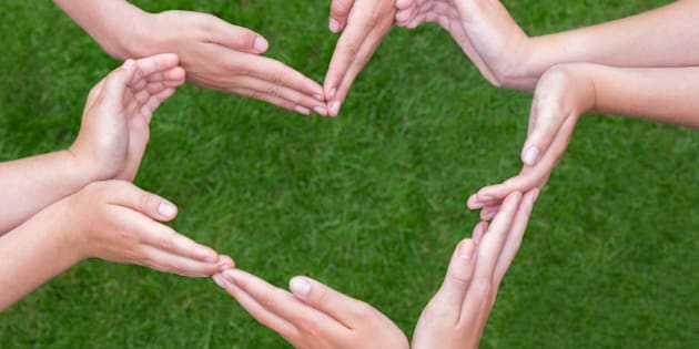 Many arms and hands of girls making heart shape above green grass. Several teens hands joining in figure isolated on green grass background. Five teenagers have bare arms stretched with hands close to each other. Concept of team, teamwork, together, group, unite, binding, bond, agreement, trust, combine, connection, contact, friends, friendship, girlfriends, play, fun, enjoy, partners, colleagues, support, motivate, love, loving, help, helping, piece