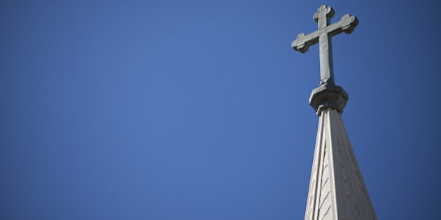 A Crucifix rises high above the skyline on top of a church's steeple.