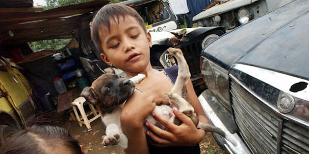 Two Filipino squatter children Jumel Alonte and her younger sister Angel (L) play with their puppy in a junkyard along a highway near the House of Representatives in suburban Quezon City 03 July 2003.  The junkyard of abandoned vehicles has been home to at least eight squatter families. The roadside junkyard will be removed on July 05 to give way for a road widening project of the Metro-Manila Developmnent Authority (MMDA).  AFP PHOTO/Romeo GACAD  (Photo credit should read ROMEO GACAD/AFP/Getty Images)