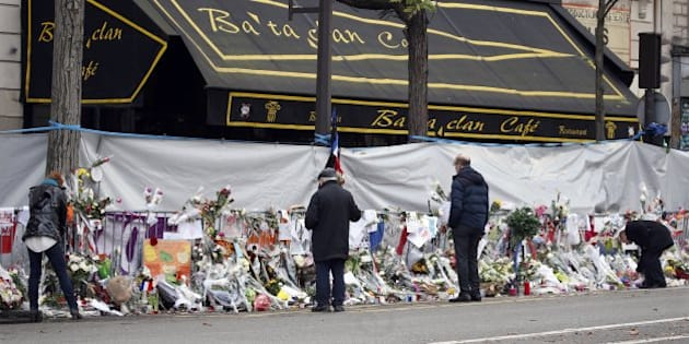 People mourn in front of the screened-off facade of the Bataclan Cafe adjoining the concert hall, one of the sites of the deadly attacks in Paris, France, November 26, 2015 a day before a ceremony to pay tribute to the 130 victims.  REUTERS/Charles Platiau