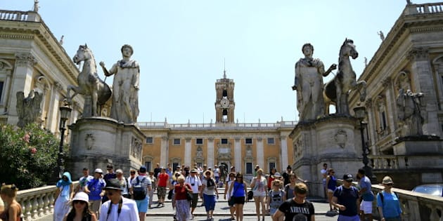 "Tourists walk in front of the Rome's city hall, ""Campidoglio"" (the Capitoline hill) in Rome July 12, 2015. Dirty and disorganised, Rome is once more in decline. City hall is paralysed by allegations of Mafia infiltration, its basic services are in tatters, the main airport is partially closed, and wild cat strikes have frayed an already ropey public transport network. For generations, the Italian capital has rested on past glories rather than built on them. The years of neglect, corruption and bureaucratic bungling have taken a fierce toll, reflecting a wider malaise that afflicts Italy as a whole.  Picture taken July 12, 2015. REUTERS/Tony Gentile"