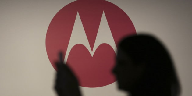A woman takes a picture in front of a Motorola logo before the worldwide presentation of the Moto G mobile phone in Sao Paulo November 13, 2013. The new Motorola phone, which is being aimed at consumers in developing markets like Brazil and India as well as budget-buyers in Western countries, is the second major new product that Motorola has developed since its acquisition by Internet company Google in 2012. REUTERS/Nacho Doce (BRAZIL - Tags: BUSINESS LOGO TELECOMS)
