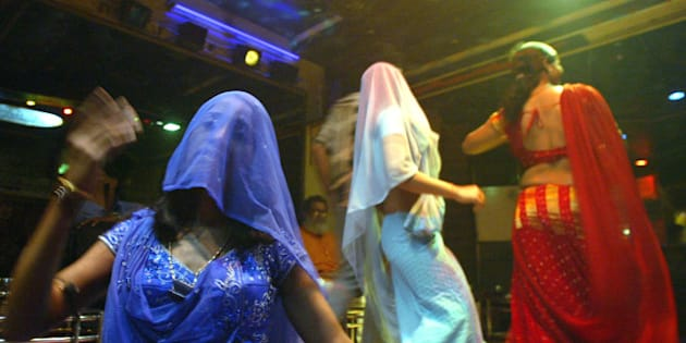 """Indian bar girls perform at a dance bar in Bombay May 5, 2005. The government of the western Indian state of Maharashtra on Wednesday endorsed the decree seeking to ban dance bars in the state. There are more than 600 dance bars in Bombay itself and the closure of cabarets is likely to render jobless more than 150,000 people across the state including dancers, waiters, bouncers and security guards. Most bars in the state employ girls, who dress in colourful costumes and dance to Bollywood songs, as customers shower them with currency bills. According to bar girl's union, the majority of the 75,000 girls working in bars will be forced into the """"flesh trade"""" due to the closure. Picture taken on May 5, 2005. REUTERS/Punit Paranjpe  AD/LD"""