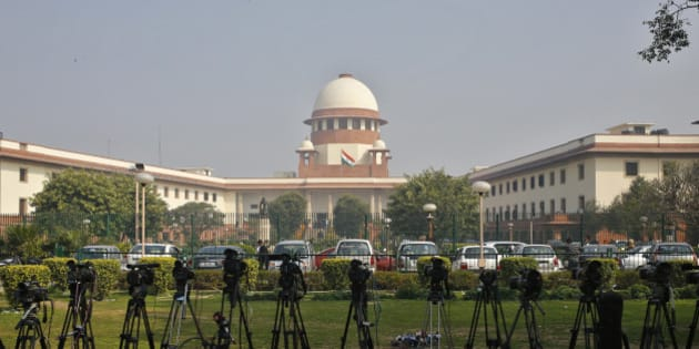 A television journalist sets his camera inside the premises of the Supreme Court in New Delhi February 18, 2014. India's Supreme Court commuted death sentences on three men for involvement in the killing of former prime minister Rajiv Gandhi to life imprisonment on Tuesday because of an 11-year delay in deciding on their petitions for mercy. Gandhi was killed by an ethnic Tamil suicide bomber while campaigning in an election in the southern Indian town of Sriperumbudur in May 1991. REUTERS/Anindito Mukherjee (INDIA - Tags: CRIME LAW POLITICS)